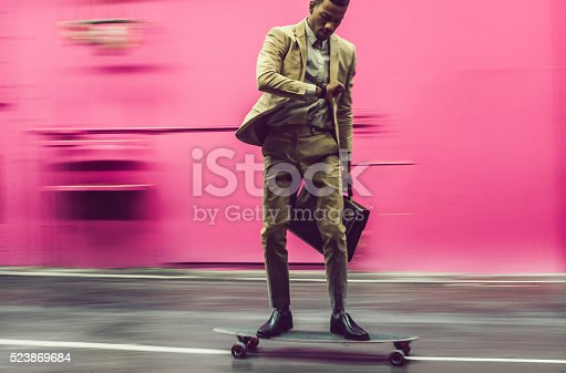 Businessman moving with skateboard by the street, Ljubljana, Slovenia