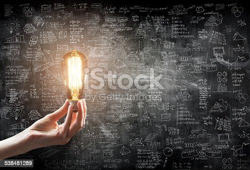 hand holding Light bulb on blackboard background hand holding or showing a light bulb in front of  business idea concept on wall backboard blackground