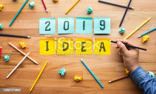 694587746 istock photo Business ideas 2019 with male hand Writing pencil on notepaper. 1069101864