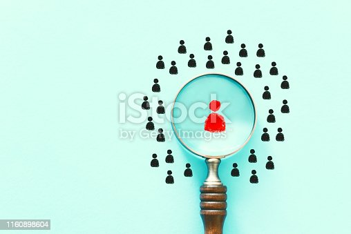 business image of magnifying glass with people icon over mint table, building a strong team, human resources and management concept
