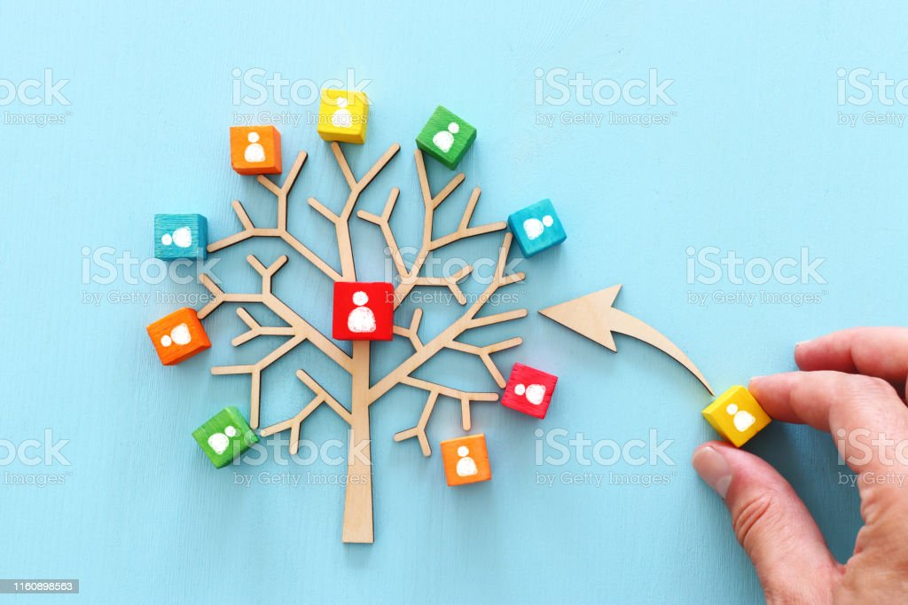 Business image of wooden tree with people icons over blue table, human resources and management concept Business image of wooden tree with people icons over blue table, human resources and management concept Backgrounds Stock Photo
