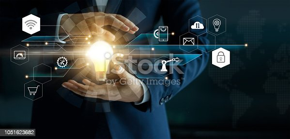 istock Business innovation technologies concept. Businessman's hand holding glowing light bulb with icon technology network connection. Futuristic digital marketing and innovative development on modern interface background. 1051623682
