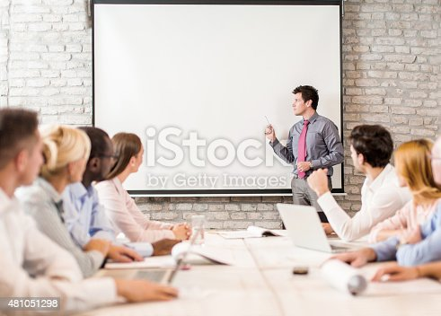 Mid adult businessman explaining something from whiteboard to large group of business people on a seminar. Copy space.