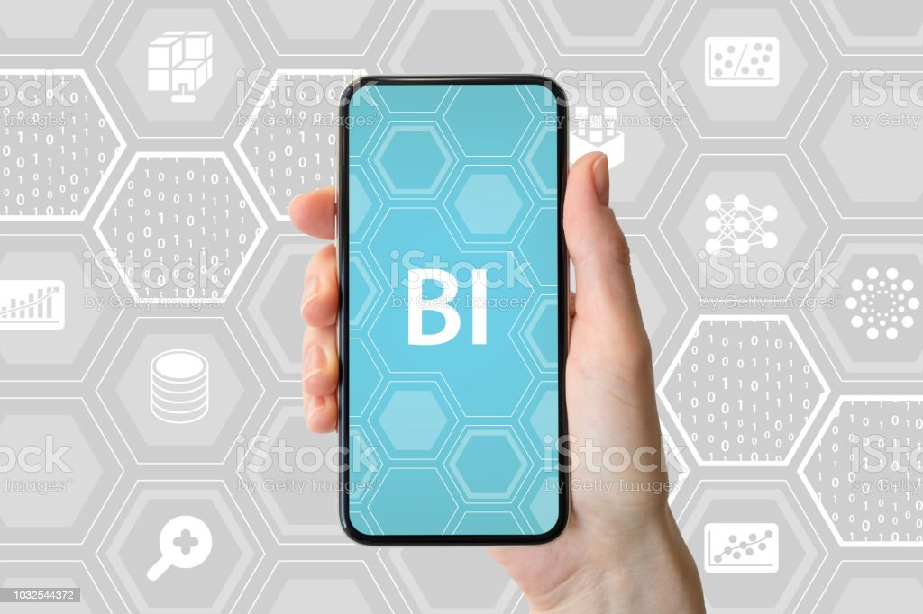 Business Intelligence concept. Hand holding modern smartphone in front of neutral background with icons. stock photo
