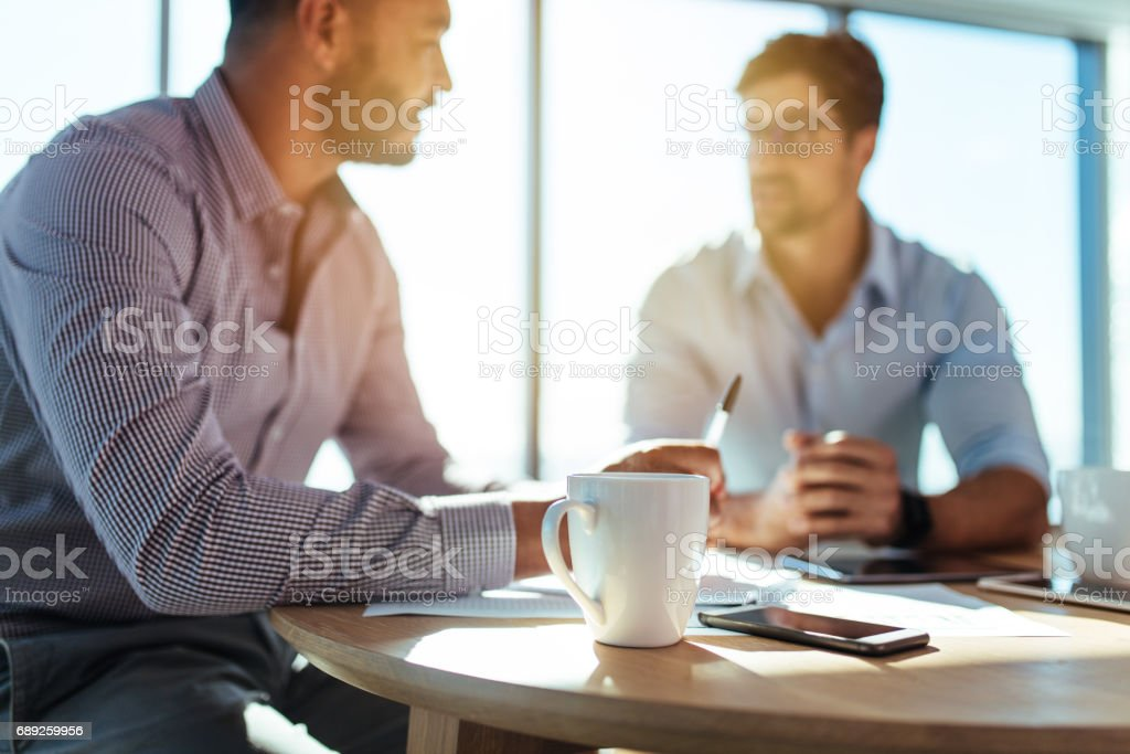 Business investors discussing business matters sitting at table in office. stock photo