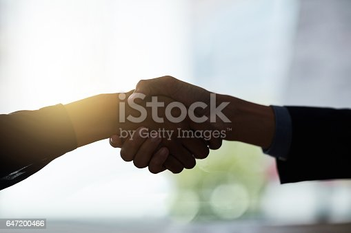 Cropped shot of two silhouetted businesspeople shaking hands in the office