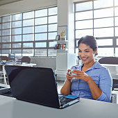 Shot of a young businesswoman drinking a beverage while using a laptop at work