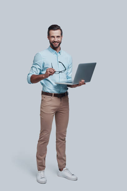 Business is his life. Full length of good looking young man carrying laptop and looking at camera while standing against grey background Business is his life. Full length of good looking young man carrying laptop and looking at camera while standing against grey background full length stock pictures, royalty-free photos & images