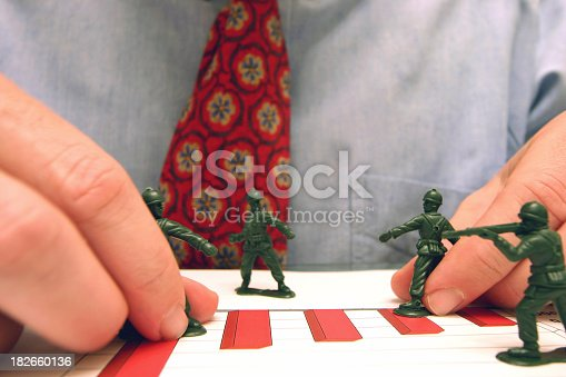 a businessman playing with army men