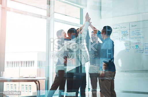 Shot of a group of young businesspeople joining hands in solidarity in a modern office