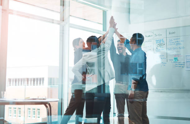 Business is winning when we stick together Shot of a group of young businesspeople joining hands in solidarity in a modern office achievement stock pictures, royalty-free photos & images