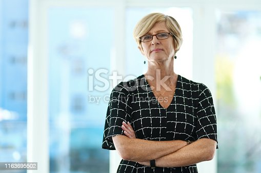 Cropped portrait of a confident mature businesswoman standing with her arms crossed in a modern office