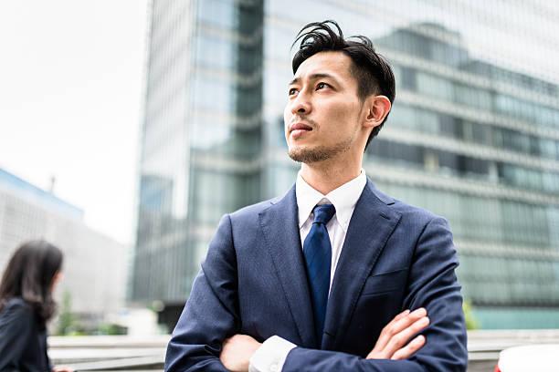 business japanese standing with arm crossed - 男性のみ ストックフォトと画像