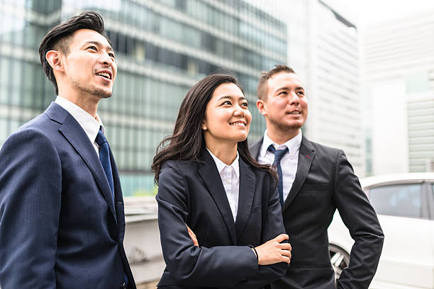 business japanese team standing togetherness - 腕組み スーツ ストックフォトと画像