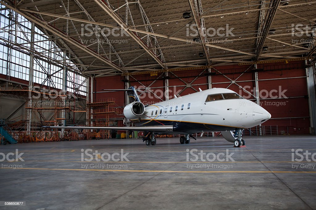 Business jet airplane stays in hangar.. stock photo