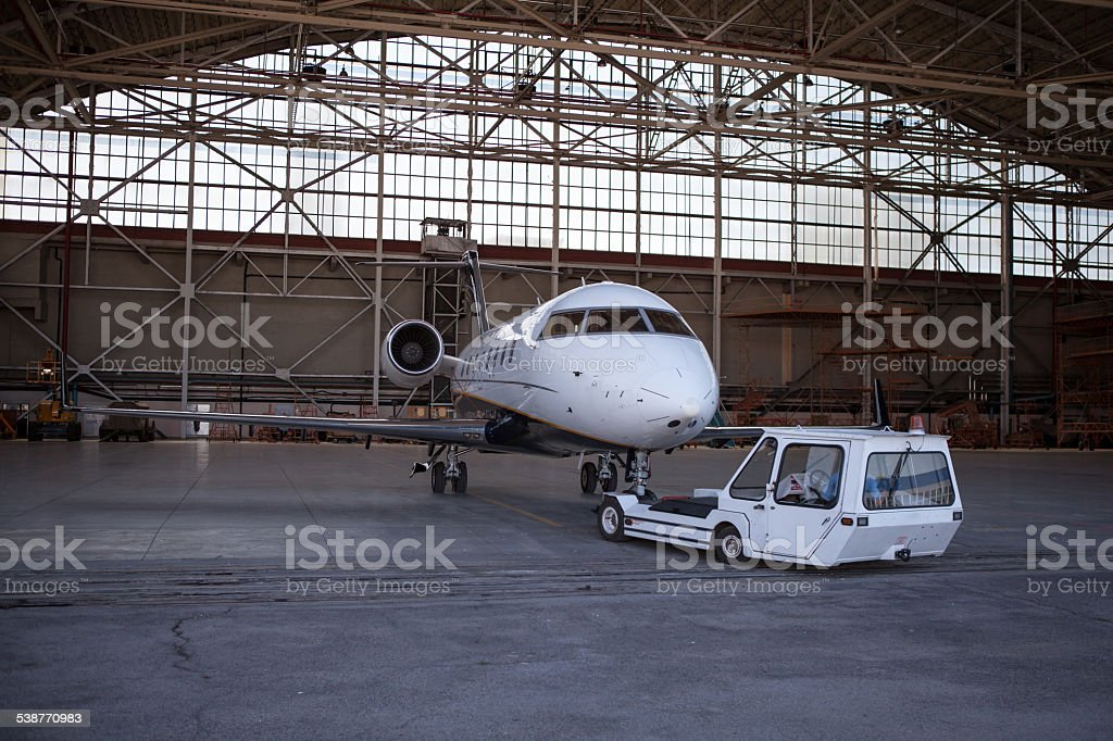 Business jet airplane stays in hangar. stock photo