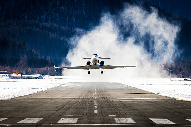 Business Jet departing a snowy airfield Business Jet departing a snowy airfield airfield stock pictures, royalty-free photos & images