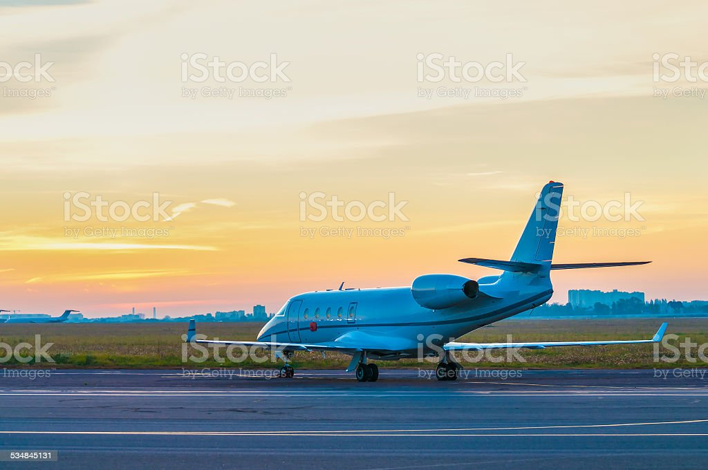 Business jet on the apron of aircraft. Dawn at airport stock photo