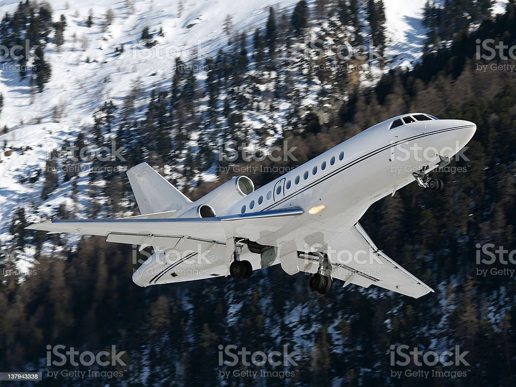 Business jet take-off with mountains stock photo