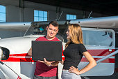 A business lady and a pilot discuss the upcoming flight by looking at the route on a laptop