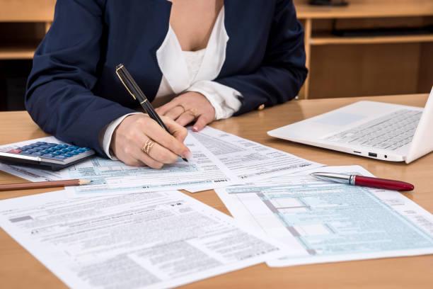 business-dame füllt das steuerformular 1040. - kindergeldantrag stock-fotos und bilder