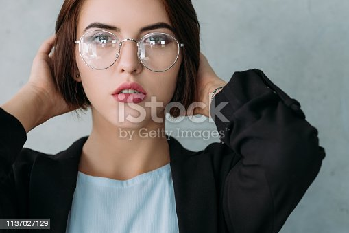 istock business lady portrait seductive look hands head 1137027129