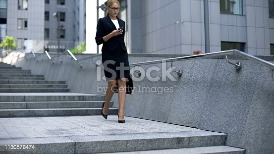 Business lady walking down stairs and texting on smartphone, careerist lifestyle