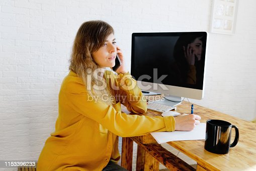 Young woman with a pen in her hand writing notes and talking on phone.