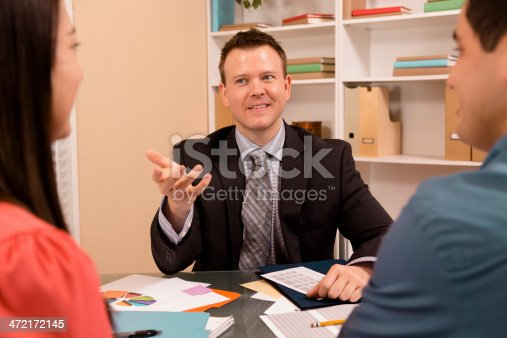 994164754istockphoto Business: Latin couple reviews financial documents with advisor. 472172145