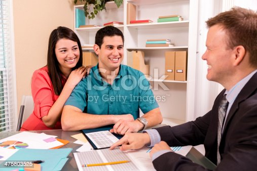 994164754 istock photo Business: Latin couple reviews financial documents with advisor. 475803525