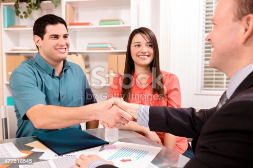 994164754 istock photo Business: Latin couple reviews financial documents with advisor. 477516545