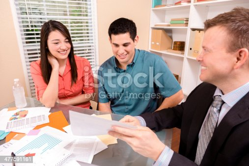 994164754istockphoto Business: Latin couple reviews financial documents with advisor. 477591161