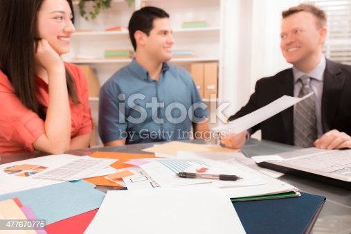 994164754istockphoto Business: Latin couple reviews financial documents with advisor. 477670775