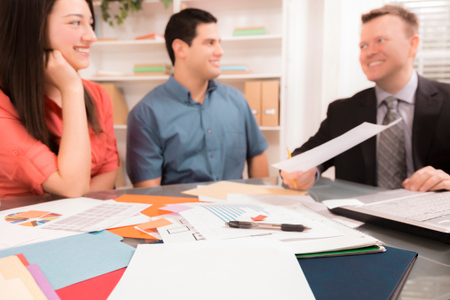 938640610 istock photo Business: Latin couple reviews financial documents with advisor. 477670775