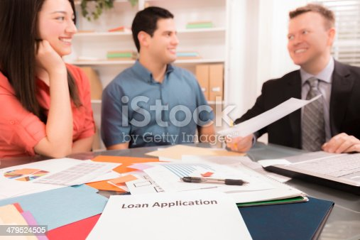994164754 istock photo Business: Latin couple reviews financial documents with advisor. 479524505