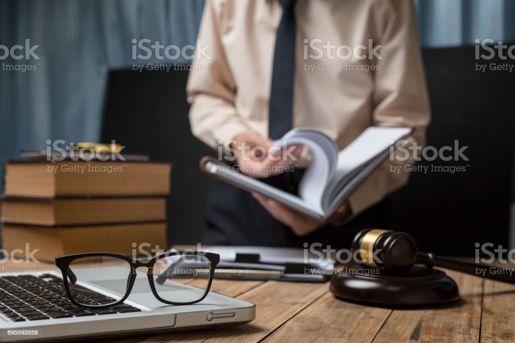 Business lawyer working hard at office desk workplace with book and documents. stock photo