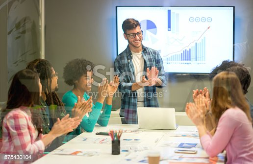 1007383644istockphoto Business leader and employees applauding someone at the board meeting for reaching the monthly sales with success 875430104