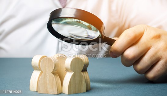 istock Business leader holding a magnifying glass over a team of workers. The concept of finding new employees. Teamliding. Team management. Hiring an employee. Human resources. Finding the employee. Scrum 1127514076