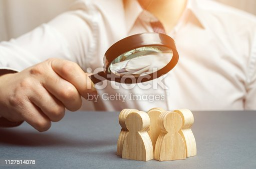 istock Business leader holding a magnifying glass over a team of workers. The concept of finding new employees. Teamliding. Team management. Hiring an employee. Human resources. Finding the employee. Scrum 1127514078