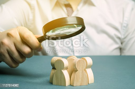 istock Business leader holding a magnifying glass over a team of workers. The concept of finding new employees. Teamliding. Team management. Hiring an employee. Human resources. Finding the employee. Scrum 1127514082