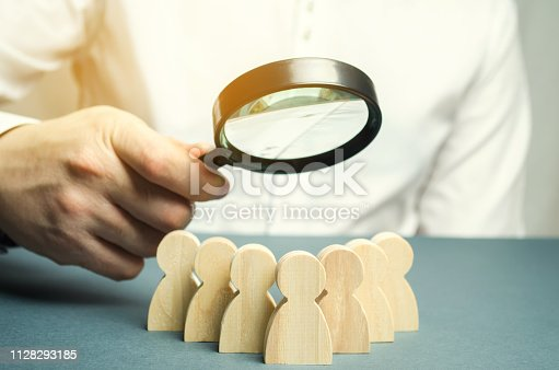 istock Business leader holding a magnifying glass over a team of workers. The concept of finding new employees. Teamliding. Team management. Hiring an employee. Human resources. Finding the employee. Scrum 1128293185