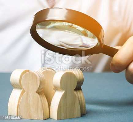 istock Business leader holding a magnifying glass over a team of workers. The concept of finding new employees. Teamliding. Team management. Hiring an employee. Human resources. Finding the employee. Scrum 1164100682