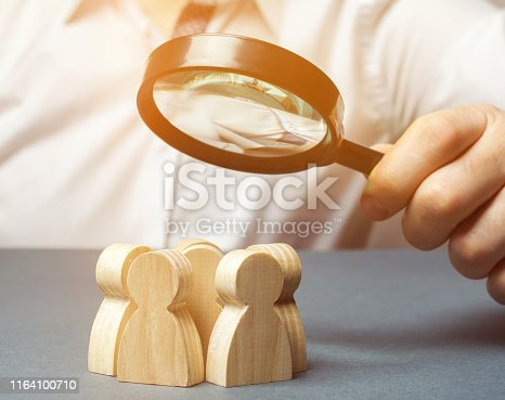 istock Business leader holding a magnifying glass over a team of workers. The concept of finding new employees. Teamliding. Team management. Hiring an employee. Human resources. Finding the employee. Scrum 1164100710