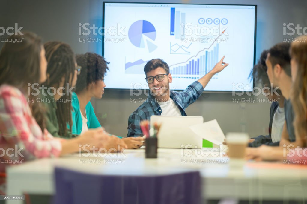 Young male business leader pointing at the screen at a board meeting...