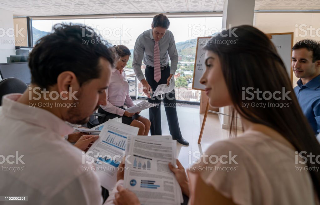 Business leader talking to female business woman while looking at a...