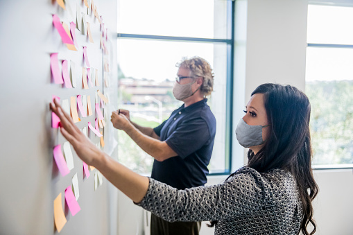 An attractive young Asian businesswoman and a mature man leading a brainstorming session by putting post it notes on the wall