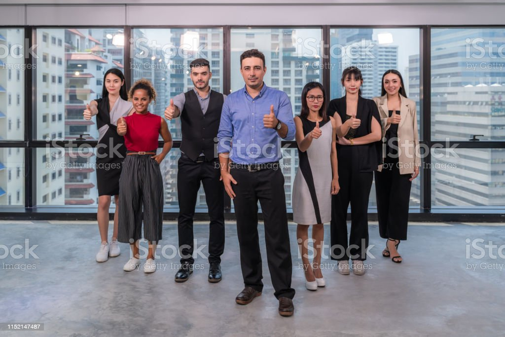 Business leaders with employees group showing thumbs up looking at...