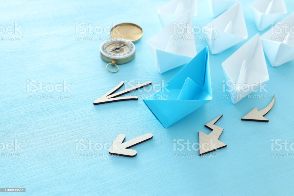 business. Leadership concept image with paper boats on blue wooden...