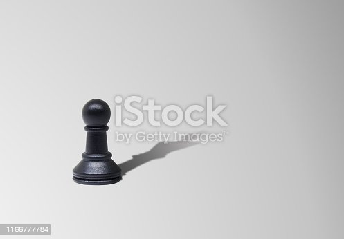 Business Leadership Concept : Pawn chess piece standing on floor with shadow shading on floor in King chess shape.