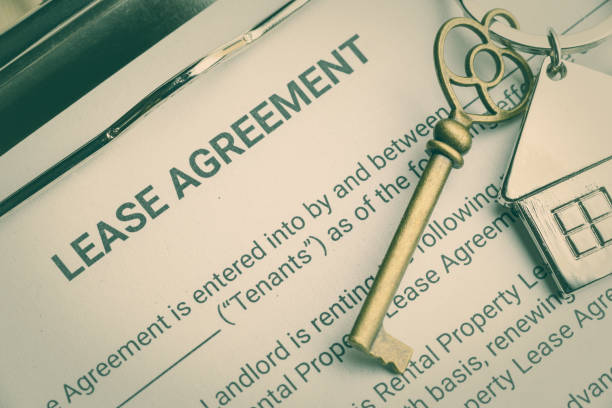 business lease agreement concept : keychain on a lease agreement form. lease agreement is a contract between a lessor and a lessee that allow lessee rights to use of a property owned by lessor - locatario foto e immagini stock